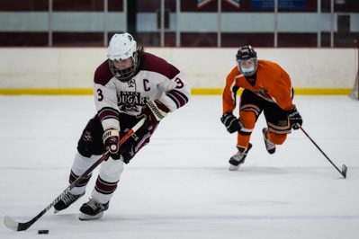 carries the puck through the neutral zone, trailed by Plattsburgh's Hunter Broadway